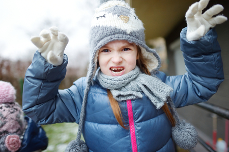 funny faces: Adorable little girl wearing winter hat making funny faces on beautiful winter day outdoors