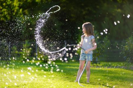 뜨겁고 화창한 여름 저녁에 정원 호스와 함께 연주 사랑스러운 작은 소녀