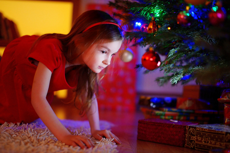 under a tree: Adorable little girl looking for gifts under a Christmas tree on Christmas eve at home