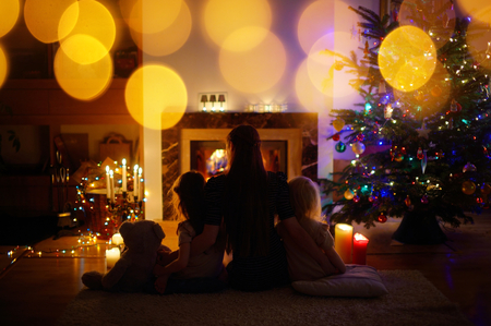 living: Young mother and her two little daughters sitting by a fireplace in a cozy dark living room on Christmas eve