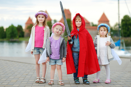 princess: Four kids dressed in princesses and a knight costumes having fun outdoors
