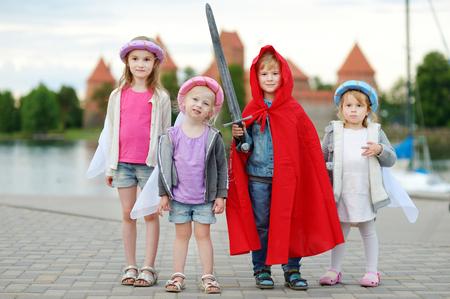 Quattro bambini vestiti di principesse e un costume cavaliere divertirsi all'aperto Archivio Fotografico