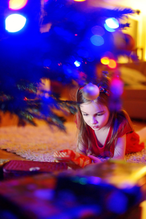 unwrapping: Adorable little girl looking for gifts under a Christmas tree on Christmas eve at home