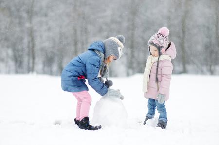 폭설 중 아름다운 겨울 공원에서 함께 눈사람을 구축하는 두 재미 사랑스러운 작은 자매