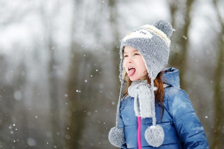 girl tongue: Funny little girl catching snowflakes with her tongue in beautiful winter park during snowfall Stock Photo