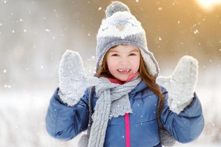 enero: Niña divertida que se divierten en el hermoso parque de invierno durante las nevadas Foto de archivo