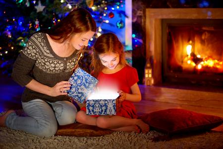 Joven madre y su pequeña hija abriendo un regalo mágico de Navidad por un árbol de Navidad en la acogedora sala de estar en invierno