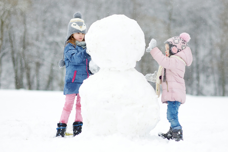 Two funny adorable little sisters building a snowman together in beautiful winter park during snowfall