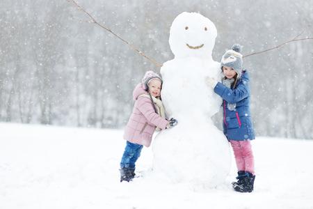 Twee grappige schattige zusjes bouwen van een sneeuwpop samen in mooie winter park tijdens sneeuwval