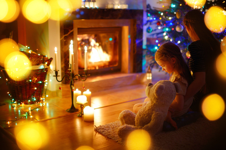 baby open present: Young mother and her little daughter sitting by a fireplace in a cozy dark living room on Christmas eve