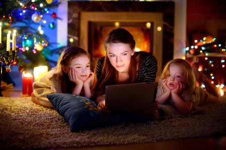 christmas movies: Young mother and her daughters using a tablet pc by a fireplace on warm Christmas evening