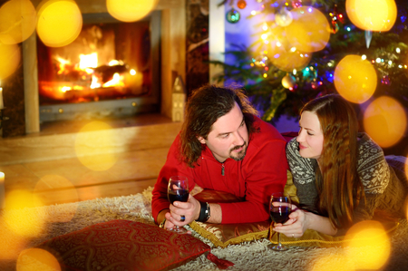 fireplace living room: Happy couple laying by a fireplace in a cozy dark living room on Christmas eve Stock Photo