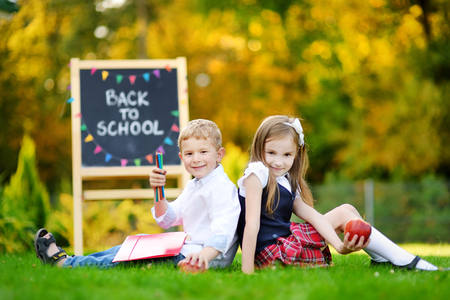 schoolkids: Two adorable little schoolkids feeling very exited about going back to school