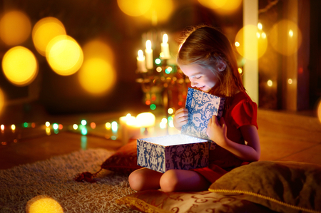 Adorable little girl opening a magical Christmas gift by a Christmas tree in cozy living room in winter Foto de archivo