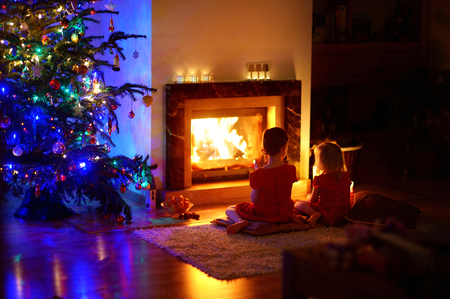 fireplace living room: Happy little girls sitting by a fireplace in a cozy dark living room on Christmas eve Stock Photo