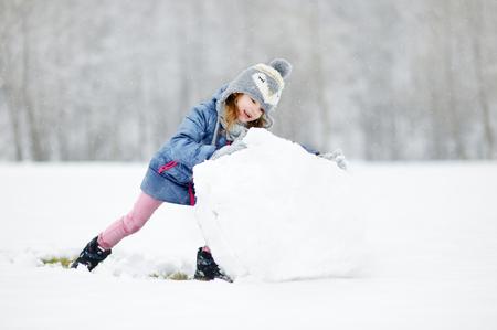 fall winter: Funny little girl having fun in beautiful winter park during snowfall