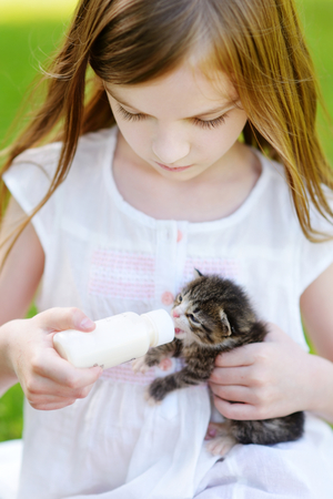 cute pussy: Adorable little girl feeding small kitten with kitten milk from the bottle at summer day