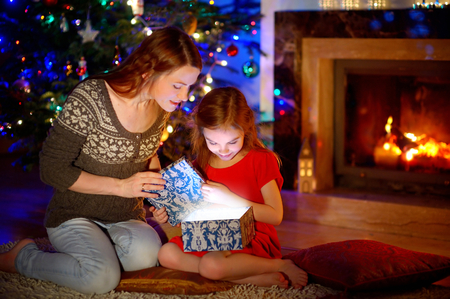 baby open present: Young mother and her little daughter opening a magical Christmas gift by a Christmas tree in cozy living room in winter Stock Photo