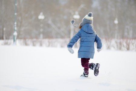 Funny little girl having fun in beautiful winter park during snowfall Reklamní fotografie - 45150277