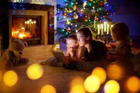Joven madre y sus hijas utilizando un Tablet PC por una chimenea en cálida noche de Navidad Foto de archivo