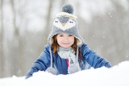 Grappig meisje met plezier in de prachtige winter park tijdens sneeuwval Stockfoto