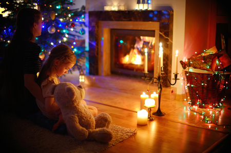 open girl: Young mother and her little daughter sitting by a fireplace in a cozy dark living room on Christmas eve