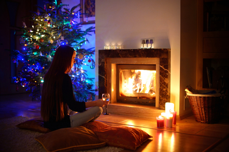 fireplace family: Woman having a drink by a fireplace in a cozy dark living room on Christmas eve