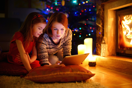 Young mother and her daughter using a tablet pc by a fireplace on warm Christmas evening