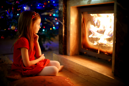 fireplace family: Happy little girl sitting by a fireplace in a cozy dark living room on Christmas eve