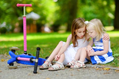 petite fille triste: Petite fille réconforter sa s?ur après qu'elle est tombée tout en montant son scooter au parc d'été