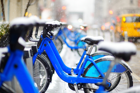 docking: Row of rental city bikes at docking station covered with snow in New York at winter