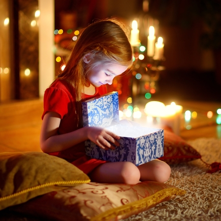 Adorable little girl opening a magical Christmas gift by a Christmas tree in cozy living room in winter Standard-Bild