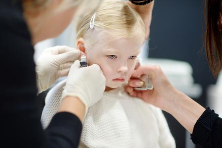 bambini pensierosi: Bambina adorabile con processo piercing all'orecchio con attrezzature speciali in centro di bellezza per l'operaio medico
