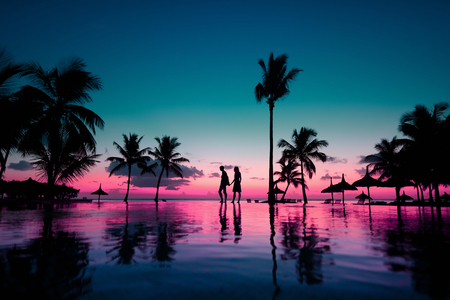 Silhouettes of young couple at scenic sunset on tropical beach