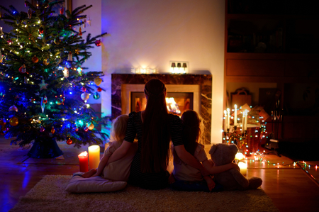 fireplace home: Young mother and her two little daughters sitting by a fireplace in a cozy dark living room on Christmas eve