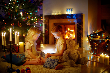 nice girl: Adorable little girls opening a magical Christmas gift by a Christmas tree in cozy living room in winter