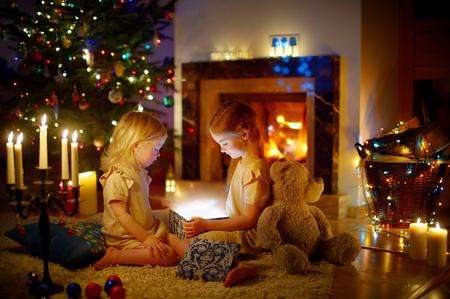 magia: Adorables niñas abren un regalo mágico de la Navidad por un árbol de Navidad en la acogedora sala de estar en invierno