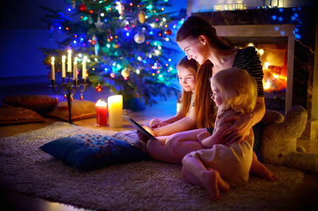 fireplace home: Young mother and her daughters using a tablet pc by a fireplace on warm Christmas evening