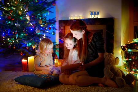 árbol genealógico: Joven madre y sus hijas utilizando un Tablet PC por una chimenea en cálida noche de Navidad Foto de archivo