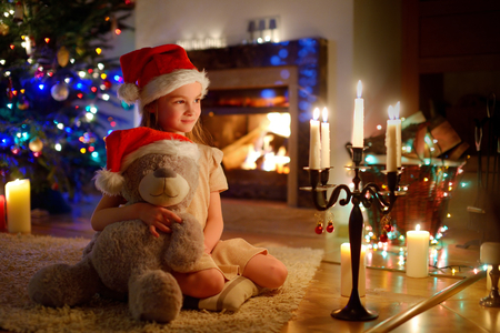 fireplace living room: Happy little girl sitting by a fireplace in a cozy dark living room on Christmas eve