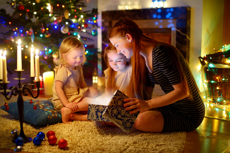 new mothers: Young mother and her two little daughters opening a magical Christmas gift by a Christmas tree in cozy living room in winter Stock Photo