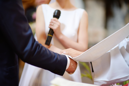 sotana: Boda católica: la novia y las manos del novio envuelto en la sotana del sacerdote Foto de archivo