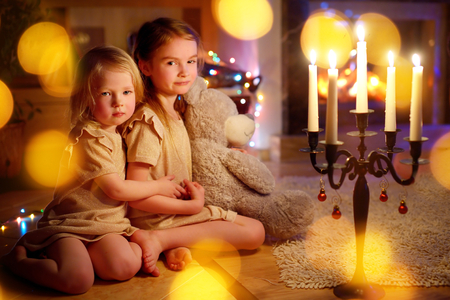 baby open present: Happy little girls sitting by a fireplace in a cozy dark living room on Christmas eve Stock Photo