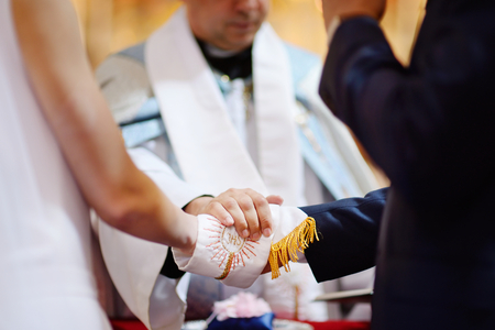 Catholic wedding: bride and groom's hands wrapped in priest's cassock