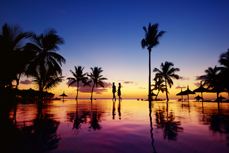sunrise beach: Silhouettes of young couple at scenic sunset on tropical beach