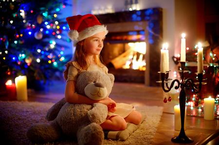 oso de peluche: Niña feliz sentada junto a una chimenea en una acogedora sala de estar oscuro en la víspera de Navidad