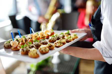 meat dish: Waiter carrying plates with meat dish on some festive event, party or wedding reception Stock Photo