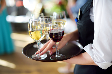 waitress: Waitress holding a dish of champagne and wine glasses at some festive event, party or wedding reception