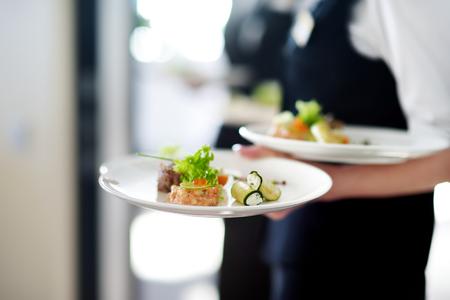 いくつかのお祭りイベント、パーティーや結婚披露宴にお肉料理のプレートを運ぶウェイター