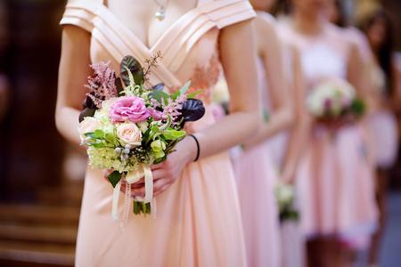Row of bridesmaids with bouquets at wedding ceremony Foto de archivo